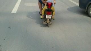 中国の路上、バイクの後ろに子供を乗せるのが危なっかしすぎる