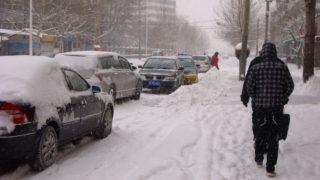 移動が困難な中国の雪の路上の仕事熱心な人