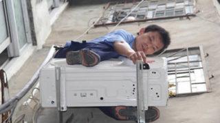 エアコンの室外機の上に乗っている危険な人