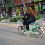 危険な乗り方の中国のバイク女性